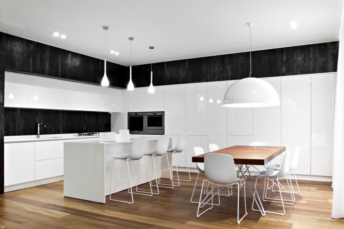 Die Küche ist mit gut definierten Mengen und Container, die alle strukturellen Elemente enthalten, in einer Palette von weißen und schwarzen Farbe, die mit den Farben des Holzes mischt. Das Wandsystem in glänzend lackiertem MDF mit Metall-Türen und Fächer für champagnerfarbene emailliertem Metall, ruht auf einem Natursteinverkleidung in Trani.