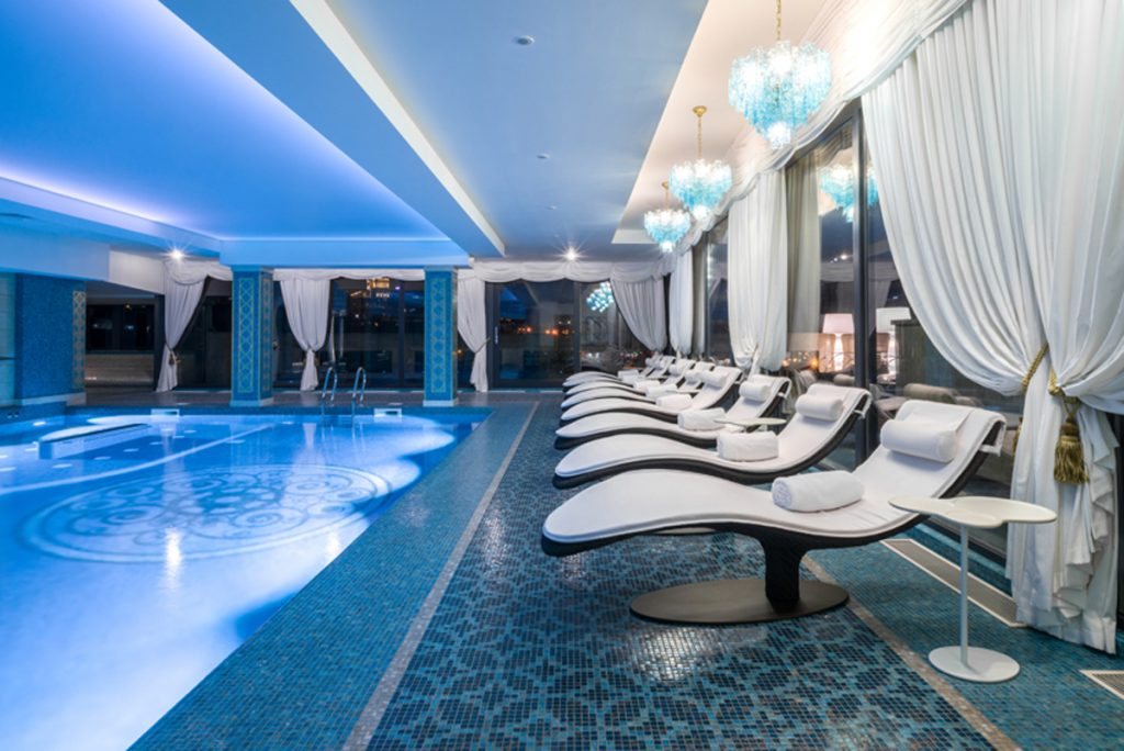 Some chaise longues on the pool edge of the spa