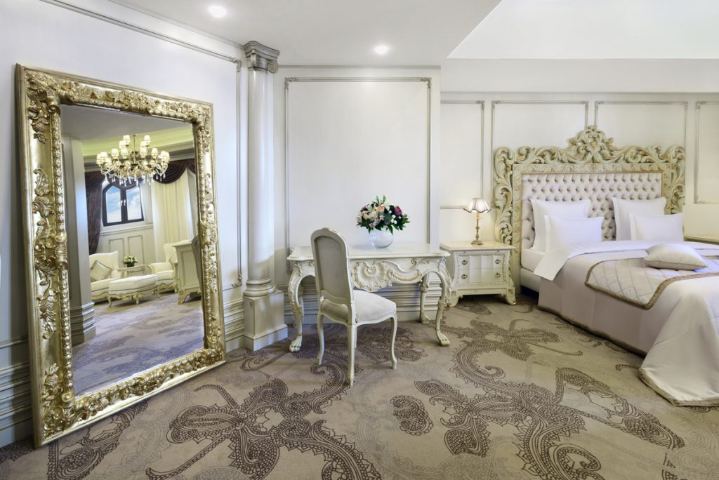 One of the Presidential Suite rooms with gold and white furnishings